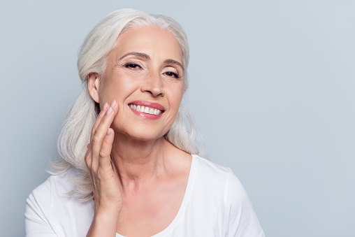 An older woman with white hair and a beautiful implant smile, touching her cheek